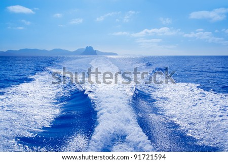 Es Vedra islet and Vedranell islands with boat wake in mediterranean Spain - stock photo