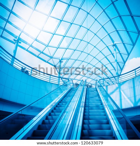 escalator and glass dome under the sky with blue tone - stock photo