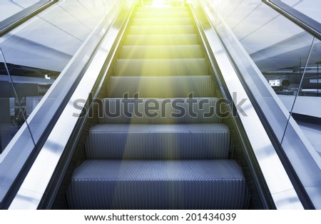 Escalator blue color tone with yellow light. - stock photo