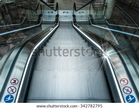 Escalator down to the light - stock photo
