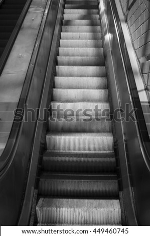 Escalator in black and white going up. - stock photo