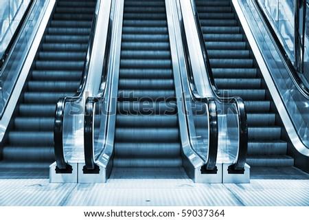 escalator in modern interior toned in blue - stock photo