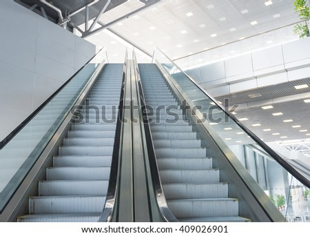 escalator in Pavilion shopping center in the room with glass