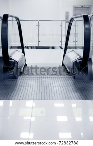 escalator in the airport,grey toning,focus on the center - stock photo