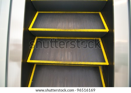 Escalator with yellow strips and glassy stair railing leading downstairs. Portrait orientation - stock photo