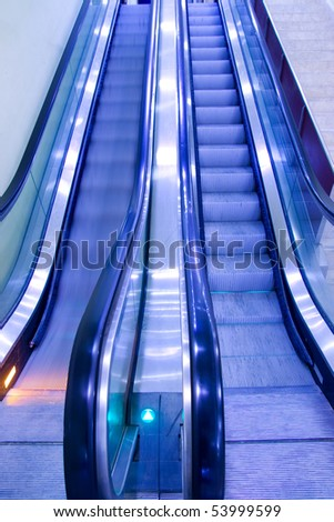 Escalators with blur showing movement, blue tint.
