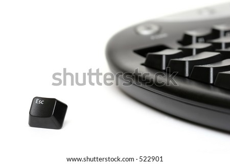 escape key escaping. shot over white with shallow depth of field with focus on single key. - stock photo