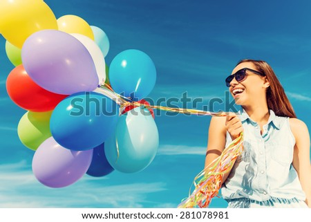 Escaping the reality.  Low angle view of joyful young woman holding colorful balloons and smiling while standing against the blue sky - stock photo