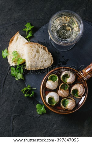 Escargots de Bourgogne - Snails with herbs butter, gourmet dish, in traditional ceramic pan with parsley, bread and glass of white wine on stone slate board over black textured background. Top view