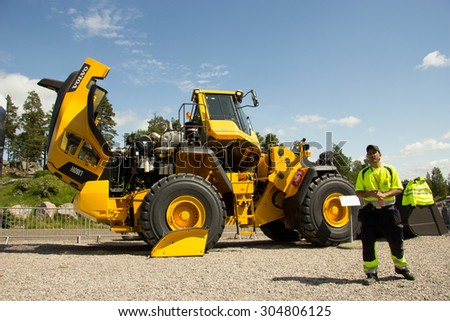 Eskilstuna, Sweden, June 25, 2015: Engeneer of Volvo CE report about loader Volvo L 180H, Volvo Days 2015, Eskilstuna - stock photo