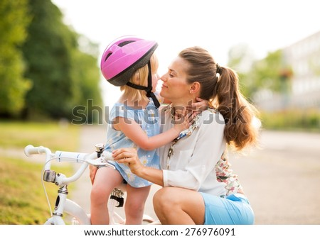 Eskimo kisses between a proud mother and daughter, who has just learned how to ride her bicycle. The mother kneels lovingly next to her daughter, holding her gently.  - stock photo