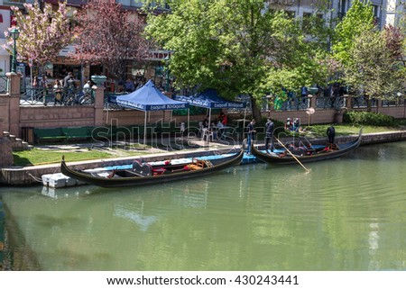 ESKISEHIR, TURKEY - APRIL 16, 2016 : View of Porsuk river flowing along the city in Eskisehir with trees and boats around on blue sky background.