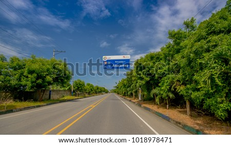 Esmeraldas, Ecuador - March 16, 2016: Paved road in the coast, with informative sign, surrounded with abundat vegetation in a sunny day in the Ecuadorian coasts