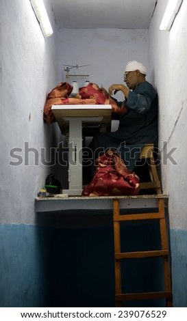 Esna, Egypt--December 2005: A cramped tailor's laboratory in the market of the village
