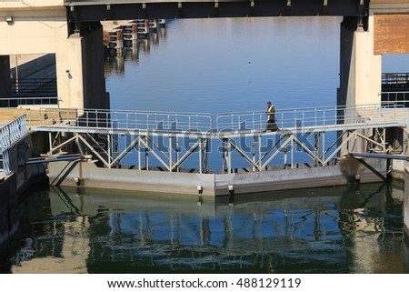 ESNA, EGYPT - FEBRUARY 3, 2016:Man walks across small bridge at the  Ship locks in Esna, and old dam on the Nile River, Egypt