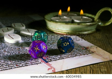 esoteric runes, astrological dice, three candles over old mystical text - stock photo