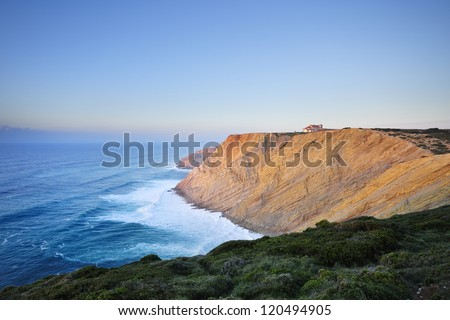 Espichel Cape cliffs, surf and sanctuary at sunset, Setubal, Portugal - stock photo