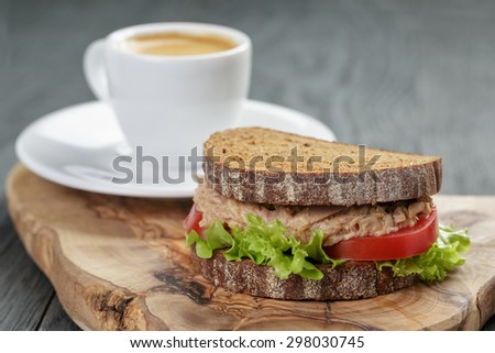 espresso and sandwich with tuna for breakfast or lunch on wood background - stock photo