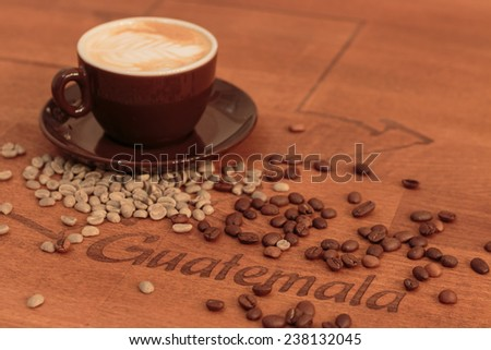 Espresso and spilled coffed beans on an egraved wooden table