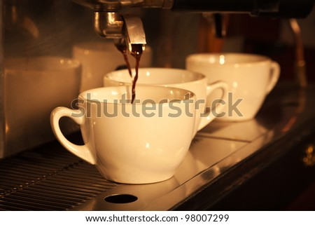 Espresso being drawn out of a professional espresso machine. Vintage look - stock photo