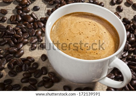 Espresso Coffee and Coffee Beans - a cup of espresso on a rustic background with coffee beans. Focus on coffee. - stock photo