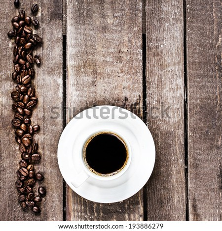 Espresso Coffee cup and roasted  coffee beans on old wooden table with copyspace,  top view. Coffee Espresso. Cup Of Coffee.   - stock photo