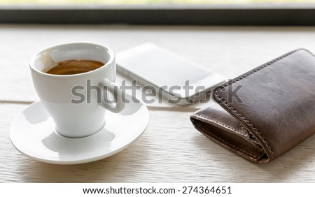 Espresso, coffee cup on table and mobile phone,wallet