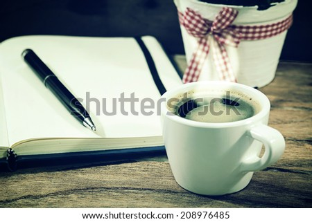 Espresso coffee cup on the table with diary and pen  - stock photo
