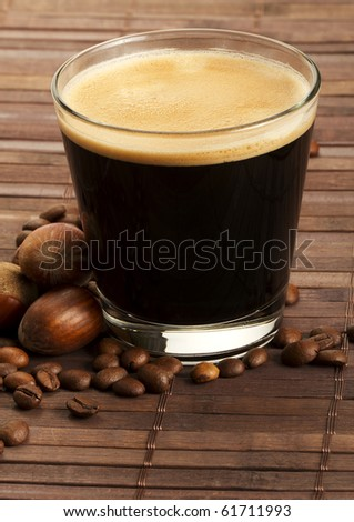 espresso coffee in a short glass with hazelnuts and coffee beans on wooden background - stock photo