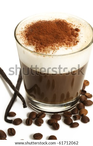 espresso coffee in a short glass with milk froth chocolate powder coffee beans and vanilla beans on white background - stock photo