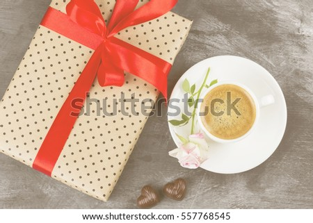 Espresso coffee in a white cup, a pink rose, a gift with a red tape and chocolates on a dark background. Top view. Food background. Toning.