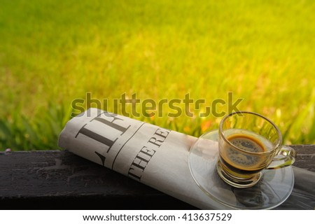 Espresso coffee in glass cup on newspaper  over blurred image of green field rice - stock photo