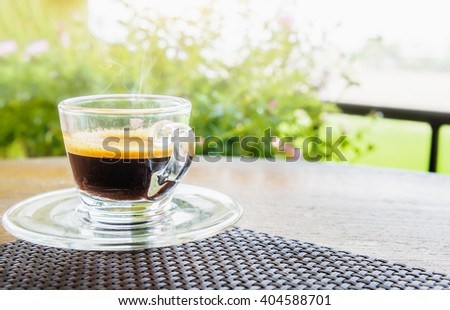Espresso coffee in glass cup on the wood table with blurred background - stock photo