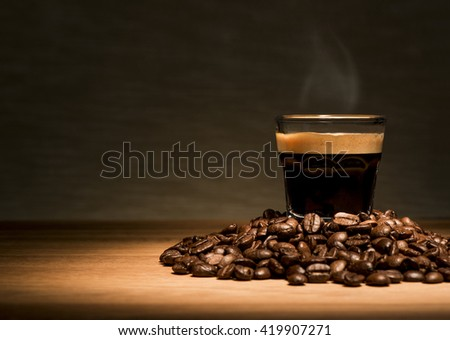 Espresso coffee with beans on a wooden table - stock photo