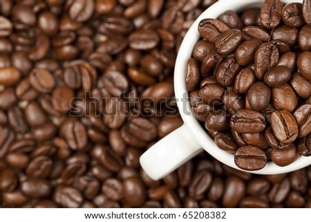 Espresso cup full with roasted coffee beans. In background are further coffee beans visible. - stock photo