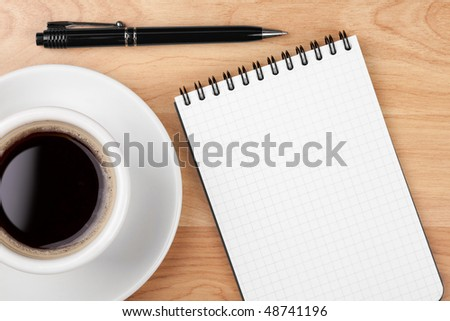 Espresso cup with blank notepad and pen on wood table - stock photo