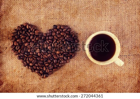 Espresso cup with coffee beans in shape heart - stock photo