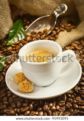 Espresso cup with fresh brewed coffee and beans - stock photo