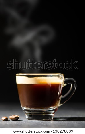 espresso in a glas steaming before dark background - stock photo