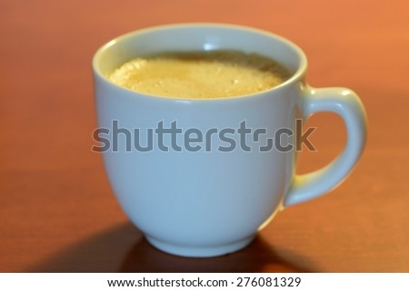Espresso in a white cup on a wooden background - stock photo