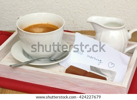 Espresso in the cup with milk and chocolate with message with text Good morning in English language, front horizontal view.Coffee and chocolate for breakfast.