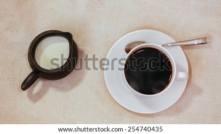 Espresso in white cup and saucer with spoon, milk in jar on grunge vintage background  - stock photo
