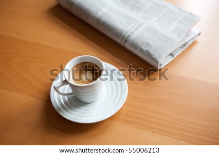 Espresso in white cup with newspaper - stock photo