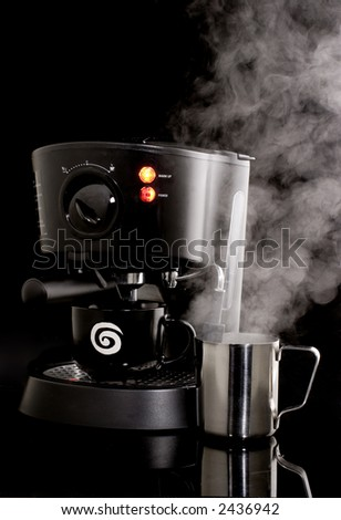 Espresso machine in use with frothing cup and steam against black background