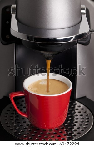 Espresso machine pouring coffee in a red cup - stock photo