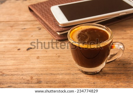 espresso shot coffee with smart phone and diary on wooden table. - stock photo