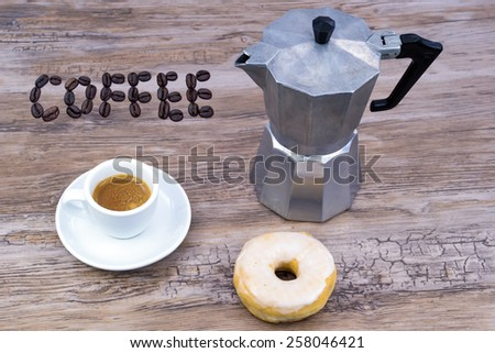 Espresso with a glazed donut on a wooden table from above with text coffee in coffee beans - stock photo
