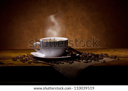espresso with smoke and cinnamon sticks on wooden table