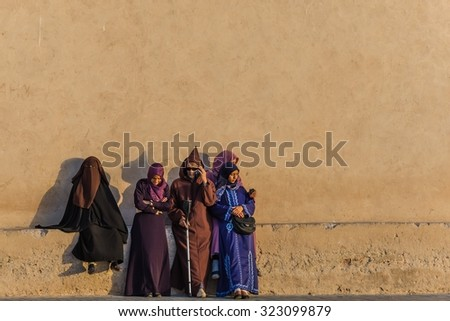 essaouira, Morocco - Circa September 2015 - arabic traditionally dressed people standing in the sunset - stock photo