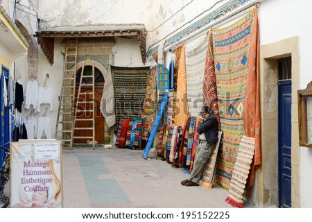 ESSAOUIRA, MOROCCO - MAY 12, 2014: Man in Morocco selling colorful rugs and carpets in the street. Essaouira, Morocco. May 12, 2014. - stock photo